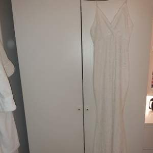 Vit långklänning från Nelly Eve. Har er extremt litet hål längst ner vid klänningens slut (sista bilden ). Frakt avgift tillkommer.