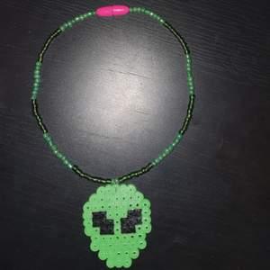 Handgjord alien choker/halsband. Gjort av glaspärlor och går att öppna och stänga. Alien är av pärlplatta. Halsbandet är stretchigt. Kan även göras i andra färgen och mptiv än just grön alien. Skickas mot fraktskostnad.