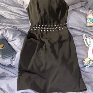 Material: fint polyester, dvs ingen stretch. Färg: svart. Strl: 34 Märke: Ginatricot. Gömd lång dragkedja i söm på ryggen, fin detalj i mitten där hud visas.