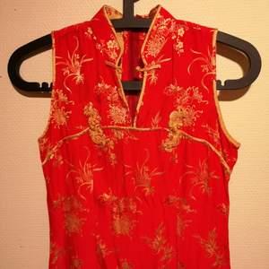 Asiatisk klänning köpt här på Plick. Lång och fin smäcker klänning! Måtten där midjan är som smalast är 33 cm gentemot längre ner på klänningen där den är 45 cm som störst. Hela klänningen är ca 130 cm lång.  Obs de sista bilderna är från tidigare säljares annons.