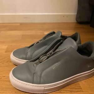 Gråa Axel Arigato skor i modellen 90s zip. Nästan aldrig använda därför i ett bra skick. En liten reva på en av skorna som syns i bilden.