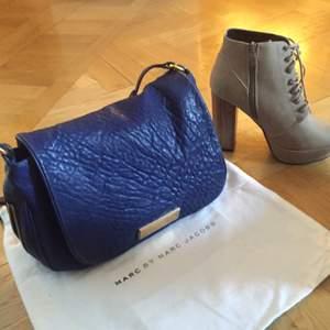 Marc by Marc Jacobs väska, nypris 4500kr. 100% läder, materialet & väskan blir snyggare ju mer man använder den. Finns ett stort fack och ett litet i. Man stänger väskan genom en magnet som är bakom det guldiga Marc märket. Axelremmen är justerbar.