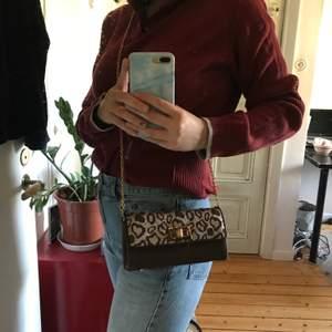Handväska i leopardmönster med gulddetaljer. Den är i ok skick och har lite söndringar här och där som är fixade. De syns på bilden, men är inget som syns när man har på sig den i verkligheten. frakt tillkommer💞