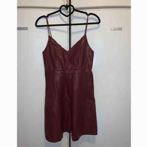 Vinröd konstläders klänning i strl S. Aldrig använd och är ny.  Frakt tillkommer med 63 kr och samfraktar gärna.