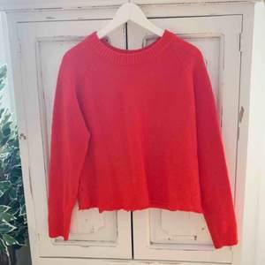 Kort stickad tröja i rödfärg