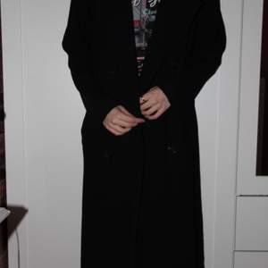 En svart lång trenchcoat i storlek 38. Säljer pga för stor för mig. Den är jätteskön och väldigt snygg när den sitter bra. Inga slitningar och använt den ca 5 ggr! Köparen står för frakten