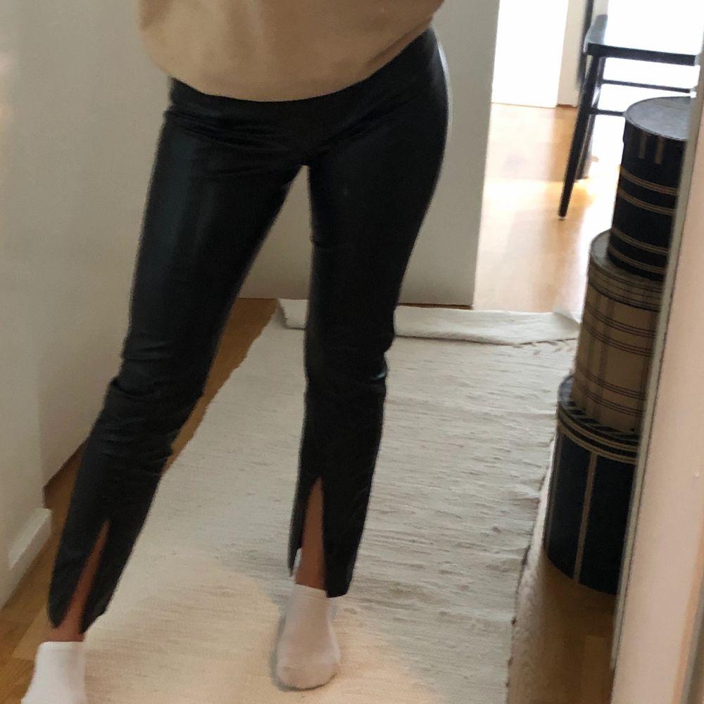 Sköna byxor från Gina i läderimitation. Slits i fram och sömmar från slits till resor. . Jeans & Byxor.