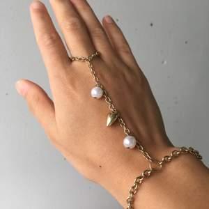 Ring armband i färgen guld med två pärlor och ett hjärta. Jag kan omplacera ringen vid handleden för att det ska passa din handled. 60kr plus 12kr frakt. Skriv om du undrar något 🧡