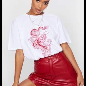 As snygg vit t shirt med rött tryck på en drake i strl S. Aldrig använd & alla lappar kvar, säljer då den inte passa mig! (Säljer även en likadan fast gul)
