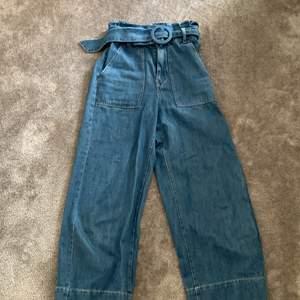 Blåa vida bershka jeans med skärp i storlek XS. Andvända några gånger men inget slitage.               (OBS) frakten är ej medräknad i priset.