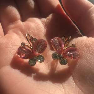Fjärilarna är rosa med silvrigt glitter i och själva örhänget är guld färgat super söta bara använt 1 gång dom rensas såklart när jag ska skicka dom:)