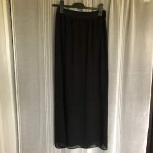 Lång kjol med en kortare innerkjol. Har en slit i den lite genomskinliga ytterkjolen. Svårt att se på bild så skriv vid mer information. Köparen står för frakt.