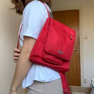 En mindre ryggsäck i röd färg. Har flertal fickor & fack. Skriv privat om ni vill ha bilder på fickorna.