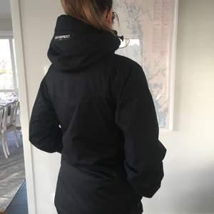 Everest skidjacka i svart med vita detaljer, bra skick. Svart kraftigt yttertyg, även midjeknäppning på insidan. Perfekt för skidåkning. Ev frakt tillkommer med ca 60 kr. Storleken är 36 men jackan är rymlig.