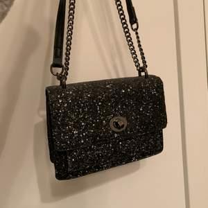 Glittrig väska från Åhléns, bra skicka man kan ha bandet kort och långt!