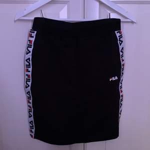 Svart kjol från fila med den populära designen på sidan. Köpt på NK i stockholm men knappt kommit till användning.