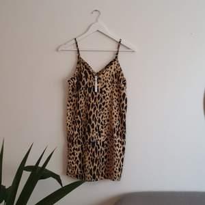Leopardmönstrad klänning, inköpt från ASOS PETITE. Banden är justerbara. Storlek 32. Aldrig använd. Fraktkostnader tillkommer.
