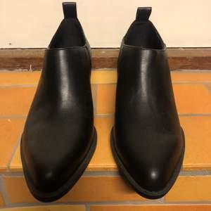 Nya oanvända låga stövletter i läderimitation.