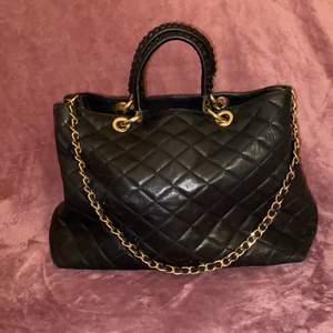 En svart handväska i äkta svart läder, med ett avtagbart axelband. Fina guld detaljer, två stora och små fack inuti. Brunt tyg på insidan. Väldigt bra skick med få repor. Väskan är från mitten av 2000-talet. ✨