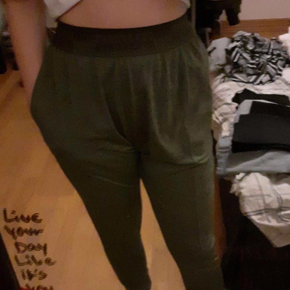 Ett par träningsbyxor som är mörkgröna och ganska stora men det ska vara så. byxorna har 2 fickor 1 per sida av byxorna. . Jeans & Byxor.