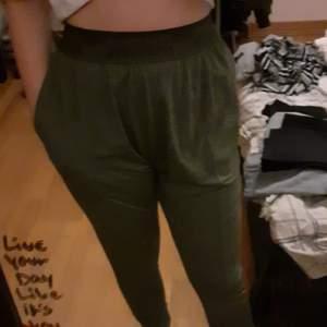Ett par träningsbyxor som är mörkgröna och ganska stora men det ska vara så. byxorna har 2 fickor 1 per sida av byxorna.
