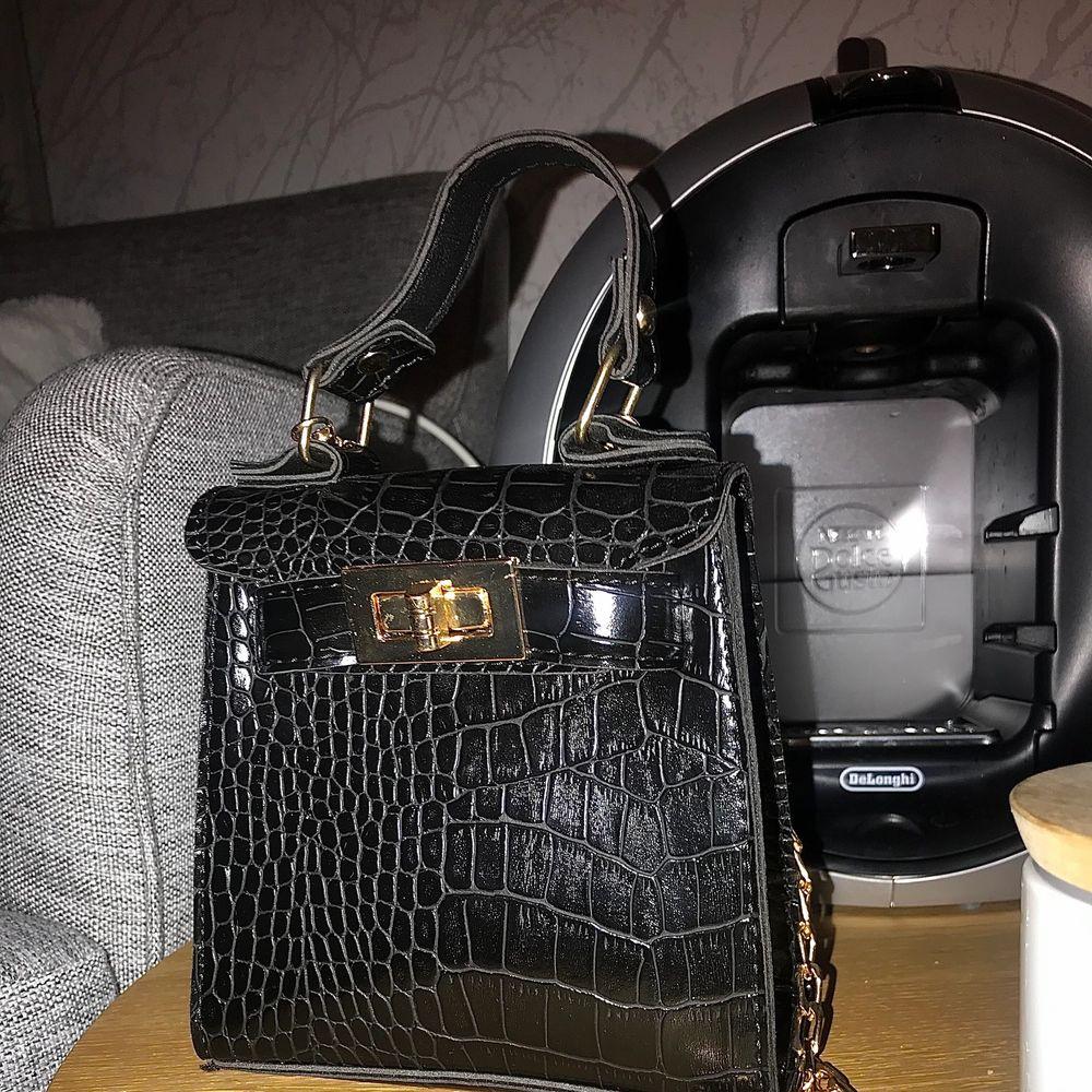 Här har ni en söt mini krokodil svart väska som passar till allt & frakten ingår i priset. (Inga returer). Väskor.