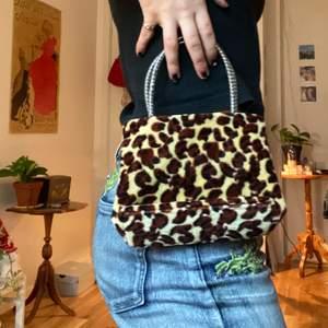Liten handväska i mjukt leopardmönstrat tyg! Om fler bilder önskas kontakta mig! Köpt på second hand