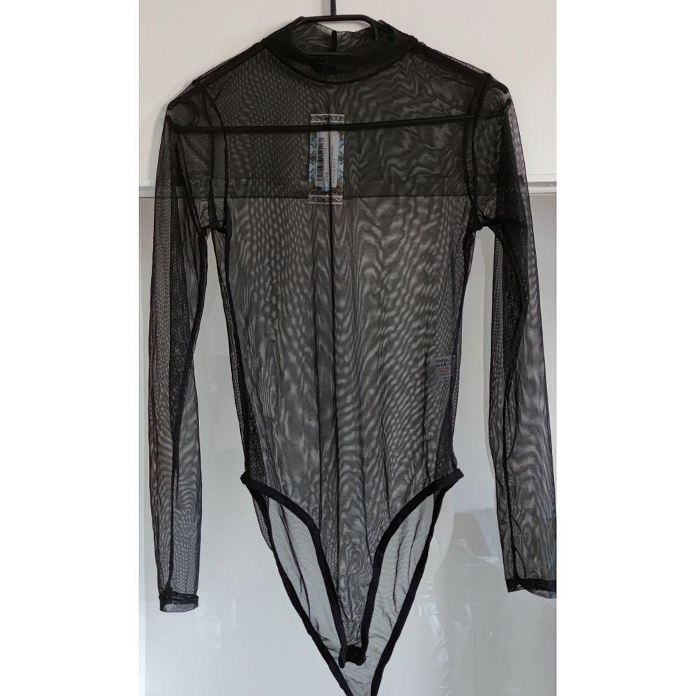 En långärmad svart mesh bodysuit som passar medium , storlek 40. Endast testad ,inte använd pga för liten och kort. Knappar för stägning i grenen.(för kort för 172cm lång kropp , passar kortare personer ). Toppar.