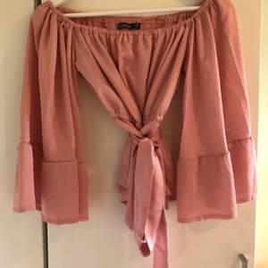 Helt ny rosa blus från Bohoo i sidenmaterial. Stl 36, passar S och Xs. Går att knyta rosett med bandet i midjan. Skickas mot fraktkostnad 44 kr.