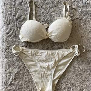Vit, mönstrad bikini med spänne bak. Bh i storlek 38 och trosorna i 40