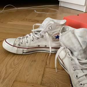 Vita converse som är ganska slitna. Gummit är lite trasigt på vissa ställen