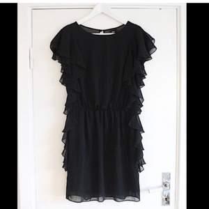Så snygg svart klänning i chiffong med volanger och öppen rygg från ASOS! Sitter så snyggt på och känns väldigt lyxig. Tyvärr har den aldrig kommit till användning så den är helt oanvänd med tags kvar. Passa på att fynda!