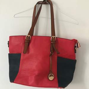 Stor och rymlig Röd och mörkblå väska från Dudlin med bruna detaljer. Fin väska som är väldigt lite använd, perfekt för skola/jobb då den rymmer dator och böcker! 100kr utan frakt Möts i Sthlm eller fraktar
