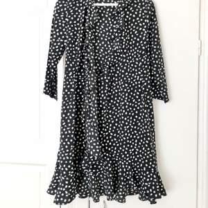 Svart omlottklänning med vita prickar från Vero Moda. Volang nedtill. Aldrig använd! Mycket fint skick. Stl S, true to size. Köparen står för frakten, 44 kr.