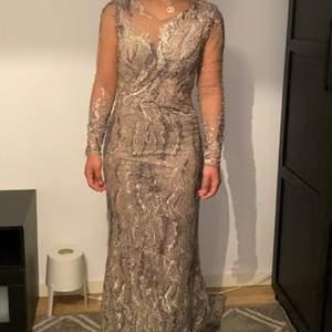 Använd en gång, beige silvrig klänning med släp och genomskinliga armar och mönster vid magen