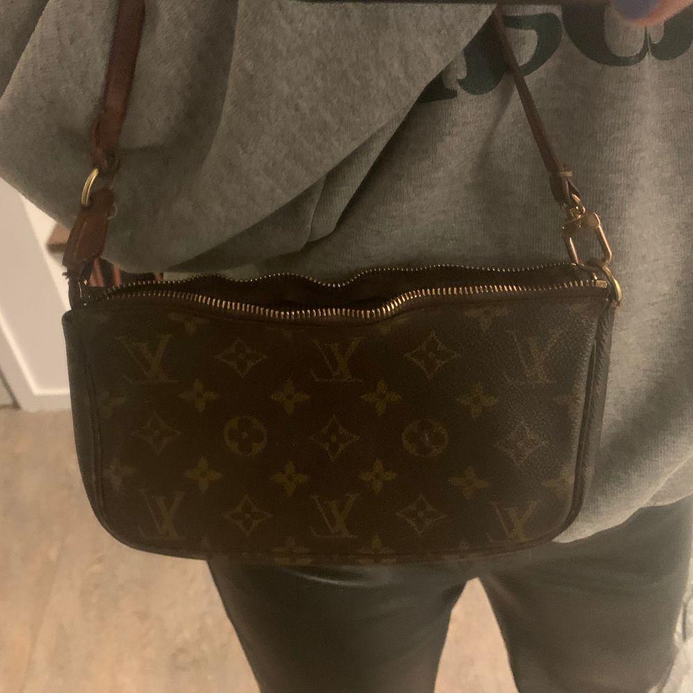Vintage Louis Vuitton pochette väska i fair skick. Draget till dragkedjan saknas men inget som stört mig (går alltså fortfarande att stänga!!!) , den har en liten buckla i kanvasen men inget märkbart. väskan är tillverkad i Frankrike runt 2001, självklart äkta!. Väskor.