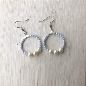 Superfina egentillverkade örhängen i en babyblå färg med större vita pärlor i mitten.