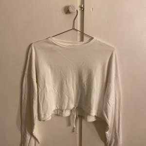 Säljer en vit croppad sweatshirt från h&m. Den har snörning på slutet av armarna och snörning i slutet av tröjan och den är i storlek XS. Fick den i present för nåt år sedan men det är inte min stil så den har inte kommit till någon användning (aldrig använd)