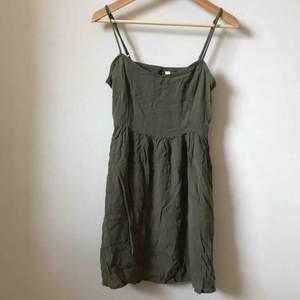 Toksöt krinklad klänning i perfekta gröna färgen. Mjukt tunt material. Endast testad, finns dock 2 ställen där sömmen släppt lite som enkelt lagas. Tvättar innan leverans. Mkt liten i storleken passar 34/xsmall. Frakt 22kr