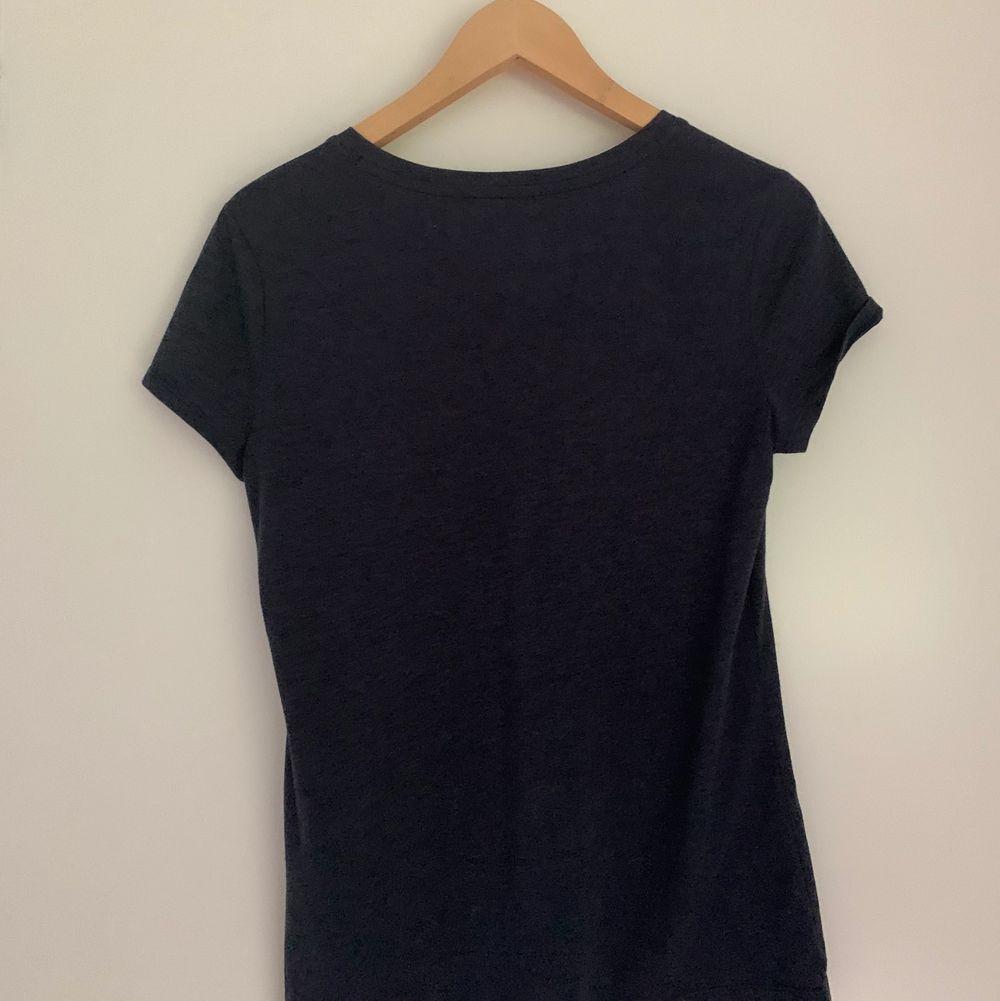 Marinblå t-shirt med guldglittrigt tryck från Tommy Hilfiger i nyskick. Classic fit i storlek S! 150kr + frakt 🪐. T-shirts.