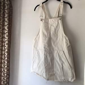 Off white hängselklänning från Pull&Bear. Fickor framtill, fransig nertill. Storlek L men är liten i storleken. Är själv S/M och den har passat perfekt. Lite kort i modellen.
