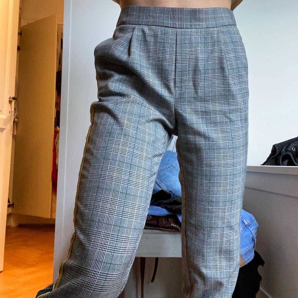 Grå, rutigt mönstrade med sträck på sidan i tre olika färger gul, vit och grön, superskönt material och mjuka. Byxorna är i bra skick, säljer pga dålig användning senaste tiden. Jeans & Byxor.