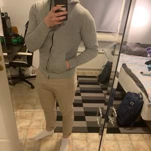 En grå Etirel hoodie med dragkedja. Använd mycket men fortfarande fräsch. Lite tight så passar nog perfekt på någon med storlek XS👍🏼 Snöret till luvan är smått trasigt men är lätt att byta om man vill. Köparen står för frakt men kan även mötas upp i Falun!🌟