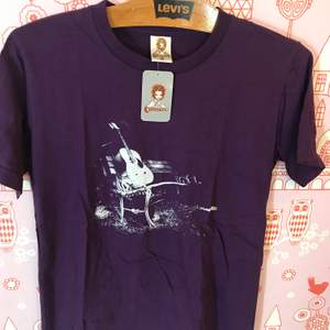 Lila T-shirt med gitarr i storlek S. Mäter 60cm på längden och 44cm på bredden. Hämtas gärna i Enskededalen.