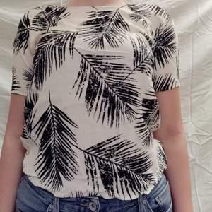 En vit blus med svarta palmblad från SOAKED i st S. Bra skick, säljes för att den kommer inte till användning. 70kr+frakt😊
