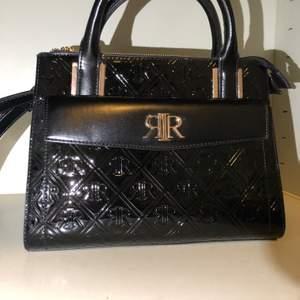 Handväska från river island med gulddetaljer, endast använd 2 ggr och därför i nyskick. Väskan har som skinn imitation där fram och slät på baksidan. De har även en axelrem så de går att ja den hängande om man vill. Extremt snygg! Köpt för 699kr