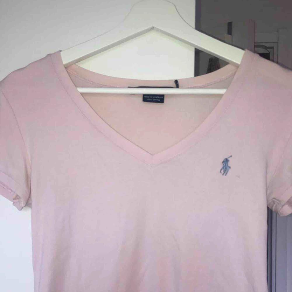 Säljer min rosa Ralph Lauren V-cut t-shirt. Den är missfärgad på en del ställen som inte syns så mycket men skriv privat så skickar jag bild. . Toppar.