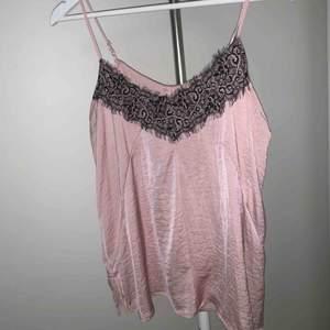 Rosa linne med svart spets upptill från NewYorker, strl S men passar någon med XS/S/M, använd ett par gånger. Finns i Hägersten/Södertälje, alternativt fraktas mot fraktkostnad.