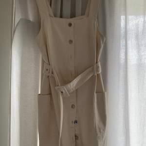 En creme vit jeansklänning från HM. Använd en gång och ser ut att vara i nytt skick! Storlek: 36 Frakt tillkommer!
