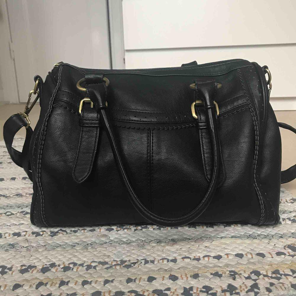 En svart even&odd väska som är knappt använd, original pris 350kr.Skinn imiterat material, två korta handtag och ett reglerbart långt band. Väskan har  två små fack med dragkedja och två mindre öppna.. Väskor.